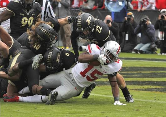 Then-freshman running back Ezekiel Elliott (15) fights for extra yardage during a game against Purdue Nov. 2 at Ross-Ade Stadium. OSU won, 56-0. Credit: Ritika Shah / Asst. photo editor