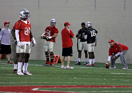 Senior quarterback Braxton Miller (5) talks with offensive coordinator and quarterbacks coach Tom Herman and redshirt-freshman quarterback J.T. Barrett (16) during spring practice March 4 at the Woody Hayes Athletic Center. Credit: Shelby Lum / Photo editor