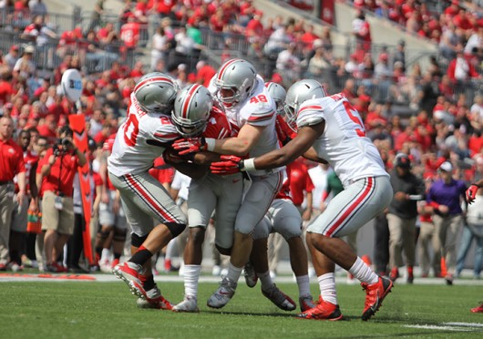 Members of the Gray defense swarm Scarlet H-back Curtis Samuel (4) during the 2014 Spring Game April 12 at Ohio Stadium. Gray won, 17-7. Credit: Shelby Lum / Photo editor