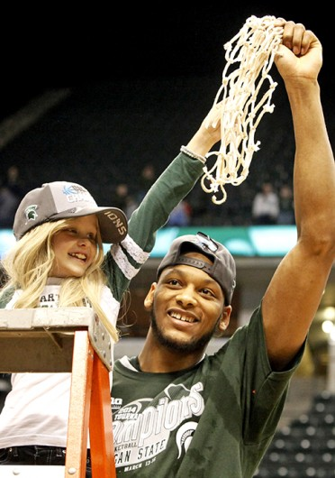 Michigan State senior center Adreian Payne (right) cuts down the nets with Lacey Holsworth after winning the Big Ten Tournament final against Michigan March 16 at Bankers Life Fieldhouse. Holsworth passed away from cancer April 9. Courtesy of MCT