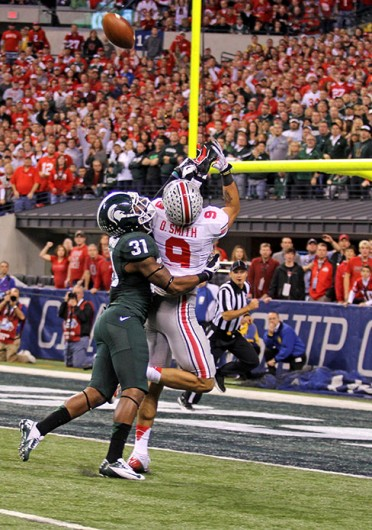Then-junior wide receiver Devin Smith (9) reaches to catch a pass with a defender on him during the Big Ten Championship Game against Michigan State Dec. 7 at Lucas Oil Stadium. OSU lost, 34-24. Credit: Shelby Lum / Photo editor