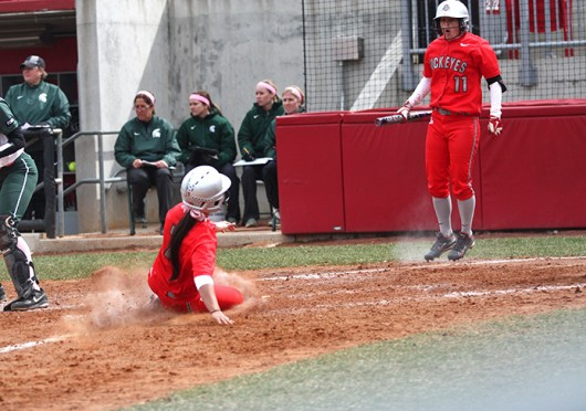 Senior second baseman Melaina Saalfeld (7) slides into home while junior outfielder Caitlin Conrad (11) celebrates during a game against Michigan State March 22 at Buckeye Field. OSU won, 11-7. Credit: Kim Dailey / Lantern photographer