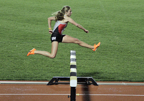 Junior distance runner Nicole Hilton jumps a fence during the 3000-meter steeplechase as part of the Jesse Owens Track Classic April 19 at Jesse Owens Memorial Stadium. Hilton won  the race. Courtesy of OSU Athletics