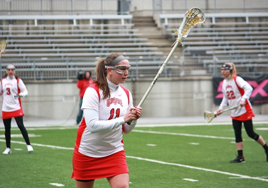 Then-sophomore attackman Katie Chase (11) warms up before a game against Notre Dame March 4, 2012, at Ohio Stadium. OSU lost, 16-7. Lantern file photo