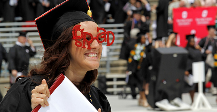 A graduate shows off her degree at the 2014 Spring Commencement, which took place at Ohio Stadium May 4. Credit: Jon McAllister / Lantern Photographer