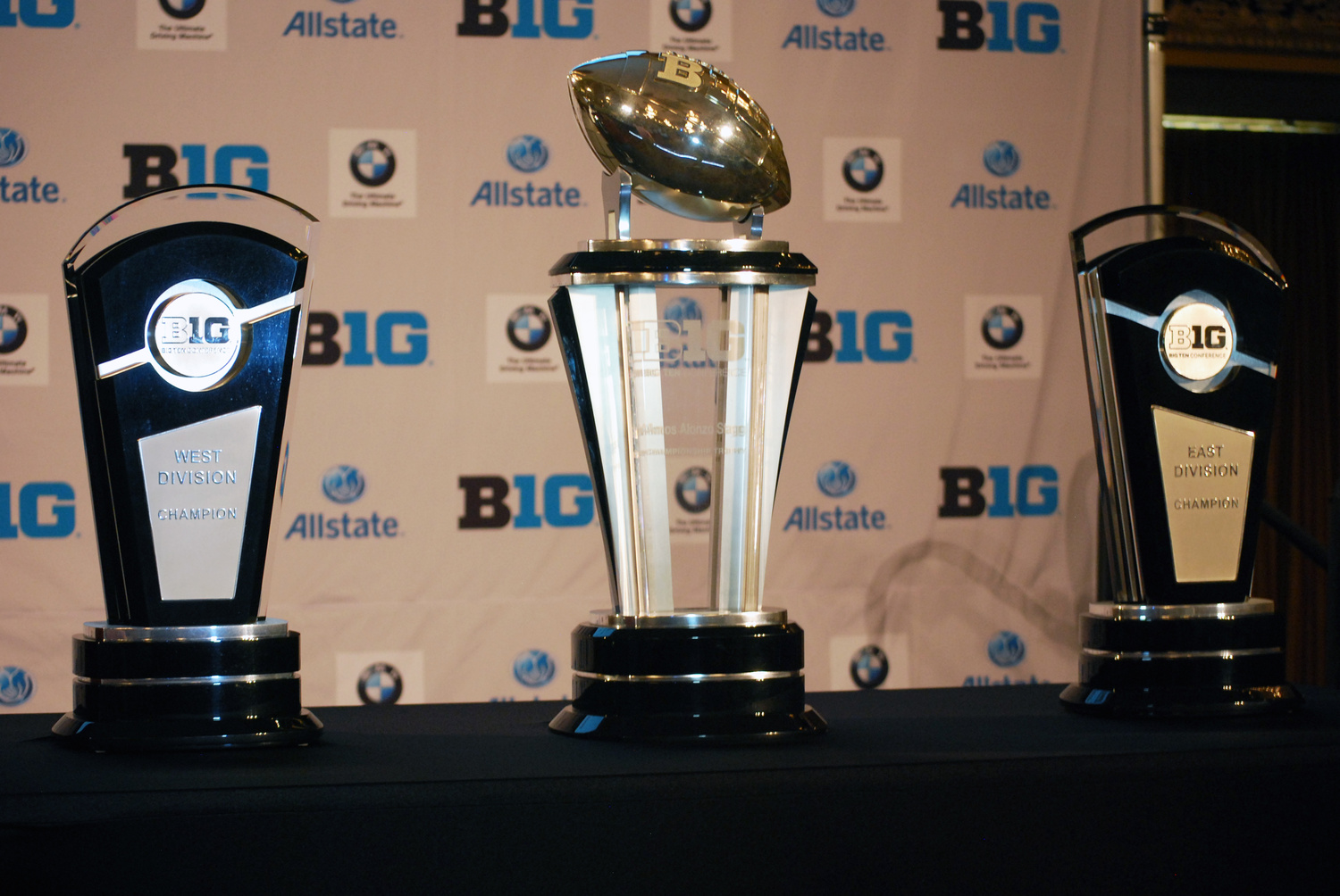 The trophies for the Big Ten West Division (left), Big Ten Championship (center) and the Big Ten East Division sit alongside the podium during the 2014 Big Ten Media Days July 28 in Chicago. Credit: Tim Moody / Lantern sports editor