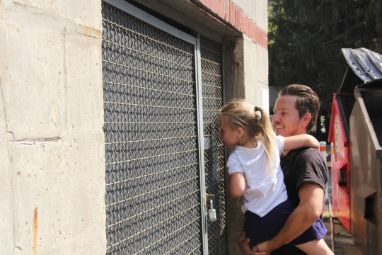 """Master's candidate Adrian Waggonner shows his daughter the projection work of fellow artist Lillianna Marie on Aug. 26, 2014. Her work, entitled """"Refrain,"""" is observable only through a peephole on a shed outside Ramseyer Hall. Credit: Daniel Bendtsen / Asst. arts editor"""