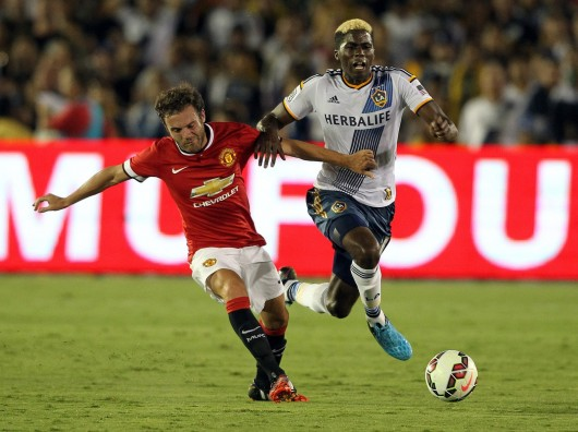 Manchester United's Juan Mata, left, and the Los Angeles Galaxy's Gyasi Zardes fight for the ball in an exhibition game at the Rose Bowl in Pasadena, Calif., on July 23. Manchester won, 7-0.  Credit: Courtesy of MCT