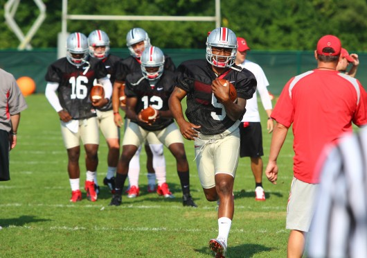 OSU senior quarterback Braxton Miller runs the ball at a practice on Aug. 9 at the Woody Hayes Athletic Center. Miller would later reinjure his right throwing shoulder and OSU announced that he would sit out the 2014 season in its entirety.  Credit: Mark Batke / Photo editor