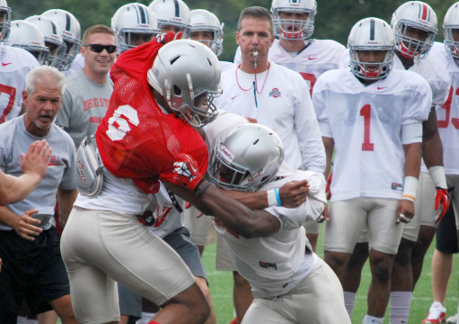 OSU coach Urban Meyer and members of the football team look on as senior cornerback Doran Grant and senior wide reciever Evan Spencer (6) go head-to-head in the circle drill during fall camp at the Woody Hayes Athletic Center Aug. 6 in Columbus. Credit: Tim Moody / Lantern sports editor