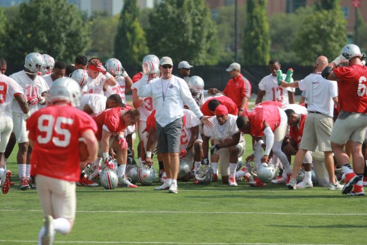 Members of the OSU football team huddle around coach Urban Meyer during the first day of fall practice Aug. 4 at the Woody Hayes Athletic Center in Columbus. Credit: Tim Moody / Lantern sports editor