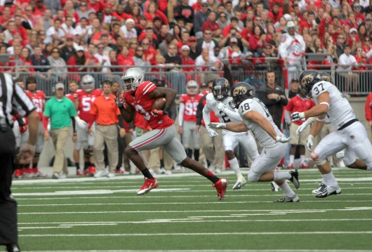 OSU redshirt-sophomore wide receiver Michael Thomas sprints away from Kent State defenders on his way to the endzone Saturday.  OSU won 66-0. Credit: Mark Batke / Photo editor
