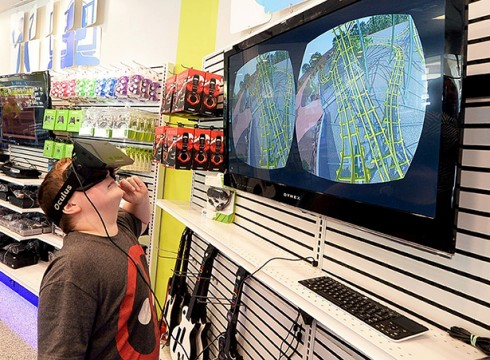 Zack Carpenter, 10, wears goggles as he tries out the Oculus Rift virtual environment setup on display, which gives a lifelike 360-degree view of a roller coaster ride, at The Grid, June 13 in Charlotte, N.C. Credit: Courtesy of MCT.