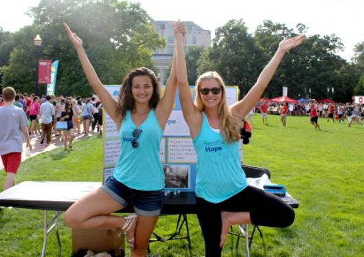 "Hannah Rinehardt, a third-year in chemistry and Breathe Hope president, and second-year health promotion, nutrition, and exercise science major and Breathe Hope's campus Yoga Instructor Hailey Schwertner hold the yoga position ""tree pose"" at the Ohio State University Student Involvement Fair to gain members for new student organization Breathe Hope on Aug. 24, 2014.  Breathe Hope is the first Ohio State student organization that aims to spread awareness and raise funds for cystic fibrosis research."