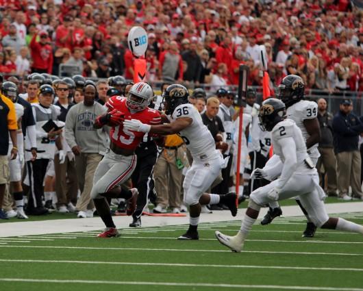 Sophomore running back Ezekiel Elliott (15) stiff arms a defender during a game against Kent State on Sept. 13 at Ohio Stadium. OSU won, 66-0.  Credit: Mark Batke / Photo editor