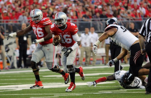 Redshirt-freshman quarterback J.T. Barrett (16) carries the ball during a game against Cincinnati on Sept. 27 at Ohio Stadium. OSU won, 50-28. Credit: Mark Batke / Photo editor
