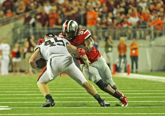 Junior linebacker Joshua Perry (37) attempts to tackle Virginia Tech sophomore fullback Sam Rogers during a game Sept. 6 at Ohio Stadium. OSU lost, 35-21. Credit: Mark Batke / Photo editor