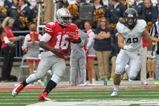 OSU redshirt-freshman quarterback J.T. Barrett (16)  carries the ball during a game against Kent State Sept. 13. OSU won 66-0. Credit: Mark Batke / Photo editor