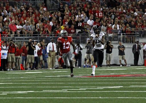 Cincinnati junior wide receiver Chris Moore (15) runs away from OSU redshirt-freshman cornerback Eli Apple (13) after making a catch during a game on Sept. 27 at Ohio Stadium. OSU won, 50-28. Credit: Jon McAllister / Asst. photo editor