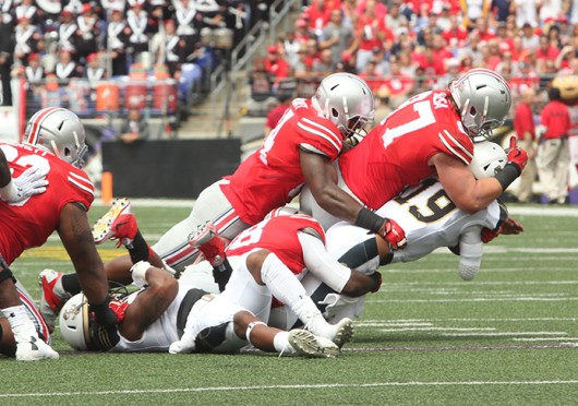 Sophomore defensive lineman Joey Bosa (97) leads a group of OSU players in tackling Navy quarterback Keenan Reynolds (19) during a game against the Midshipmen Aug. 30 at M&T Bank Stadium in Baltimore. OSU won, 34-17. Credit: Mark Batke / Photo editor