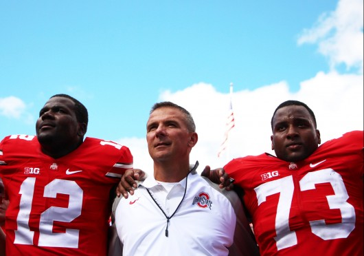 OSU coach Urban Meyer sings 'Carmen Ohio' with redshirt-sophomore quarterback Cardale Jones (12) and redshirt-junior offensive lineman Antonio Underwood (73) after the Buckeyes' 66-0 win against Kent State on Sept. 13 at Ohio Stadium. Credit: Chelsea Spears / Multimedia editor