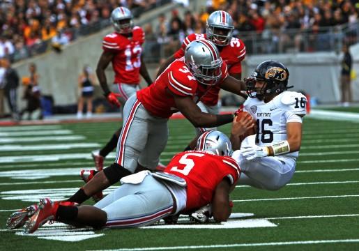 OSU junior linebacker Joshua Perry (37) and freshman linebacker Raekwon McMillan (5) tackle Kent State redshirt-freshman quarterback Nathan Strock (16) during a game Sept. 13 at Ohio Stadium. OSU won, 66-0, before heading into a bye week. Credit: Mark Batke / Photo editor