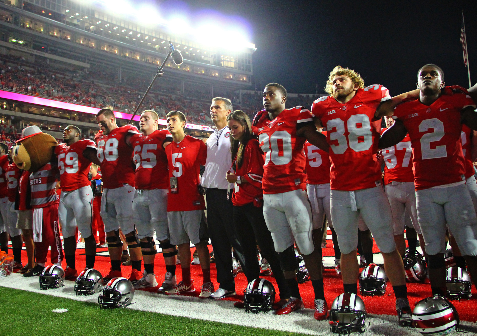 OSU coach Urban Meyer (white jacket), two of his children and members of the OSU football team sing 'Carmen Ohio' after the Buckeyes' 35-21 loss to Virginia Tech on Sept. 6 at Ohio Stadium. Credit: Mark Batke / Photo editor