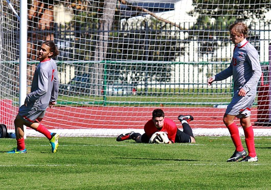 Ohio State senior goalkeeper Alex Ivanov (center) makes a save as temmates Yianni Sarris (left) and  Ryan Ivancic (right) look on during a match against Cleveland State on Sunday, October 27, 2013 at Jesse Owens Memorial Stadium in Columbus, Ohio. The win gave Ivanov his seventh shutout of the 2013 season. Credit: Mark Batke / Photo editor