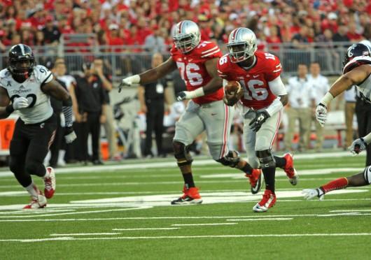 Redshirt-freshman quarterback J.T. Barrett (16) runs the ball during a game against Cincinnati on Sept. 27 at Ohio Stadium. OSU won, 50-28, behind 409 yards of total offense from Barrett.  Credit: Mark Batke / Photo editor