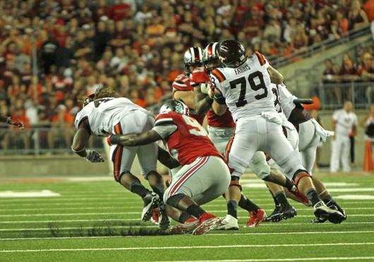 Junior defensive lineman Adolphus Washington (92) tackles a Virginia Tech player during a game Sept. 6 at Ohio Stadium. OSU lost, 35-21. Credit: Mark Batke / Photo editor