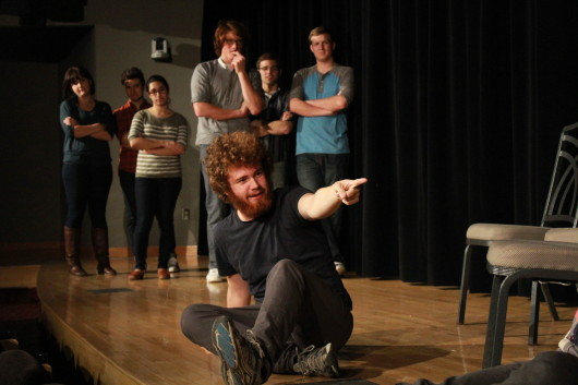 Then fourth-year in biomedical engineering Stephen Doughten sits on stage as other Fishbowl Improv members look on at the Bellwether Improv Festival Nov. 8 at the Ohio Union. Credit: Mark Batke / Photo editor