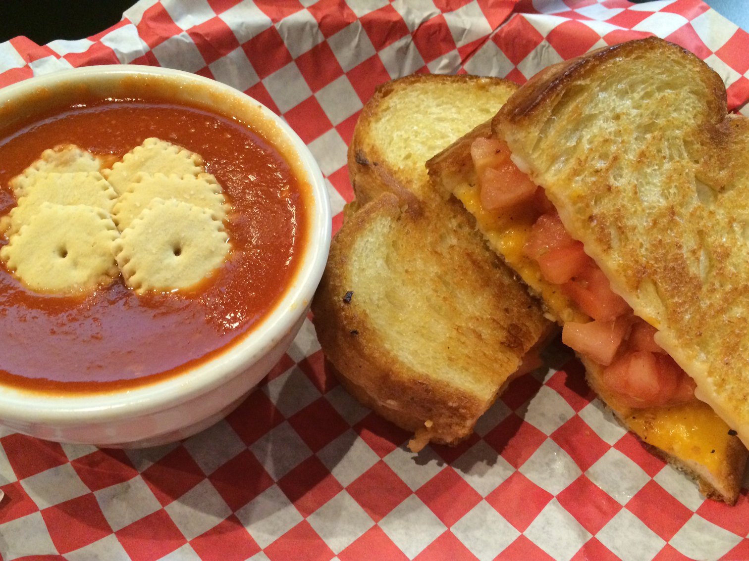 The Tom + Chee is a sandwich consisting of sourdough, cheddar, mozzarella, tomatoes, garlic seasoning, served with tomato soup. Credit: Courtesy of Courtesy of Tiffany Owen