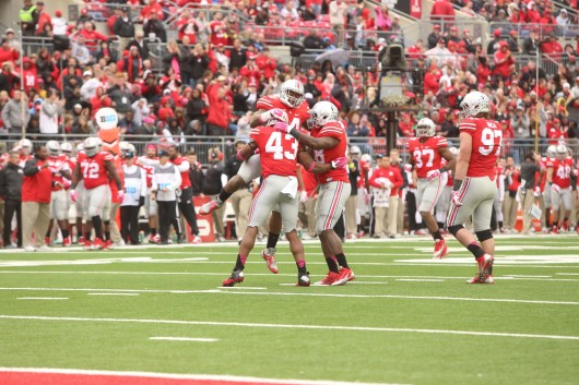 Redshirt-freshman linebacker Darron Lee (43) celebrates with senior linebacker Curtis Grant (14) and senior defensive lineman Steve Miller (88) during a game against Rutgers on Oct. 18 at Ohio Stadium. OSU won, 56-17. Credit: Mark Batke / Photo editor