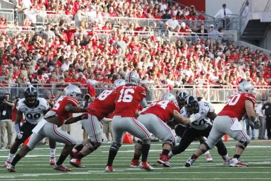 Redshirt-freshman quarterback J.T. Barrett (16) hands the ball off to sophomore running back Ezekiel Elliott (15) during a game against Cinicinnati on Sept. 27 at Ohio Stadium. OSU won, 50-28. Credit: Jon McAllister / Asst. photo editor