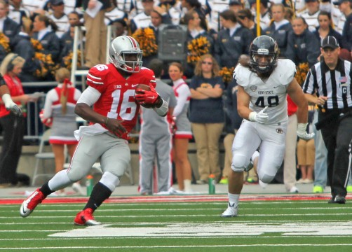 Redshirt-freshman quarterback J.T. Barrett (16) carries the ball during a game against Kent State on Sept. 13 at Ohio Stadium. OSU won, 66-0, as Barrett tied a school record with six touchdown passes. Credit: Mark Batke / Photo editor