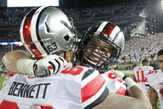 Sophomore defensive lineman Joey Bosa (right) hugs senior defensive lineman Michael Bennett following a game against Penn State on Oct. 25 in State College, Pa. OSU won in double-overtime, 31-24. Credit: Mark Batke / Photo editor