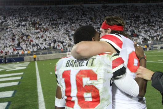 Sophomore defensive lineman Joey Bosa (right) hugs redshirt-freshman quarterback J.T. Barrett following a game against Penn State on Oct. 25 in State College, Pa. OSU won in double-overtime, 31-24. Credit: Mark Batke / Photo editor
