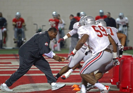 OSU defensive line coach Larry Johnson (left) works with members of the defensive line during spring practice March 20 at the Woody Hayes Athletic Center. Credit: Mark Batke / Photo editor