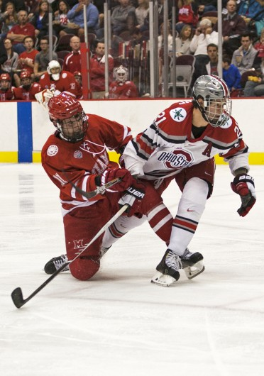 Junior defenseman Sam Jardine (21) fights past a Miami (Ohio) defender during a game on Oct. 17 at the Schottenstein Center. OSU lost, 5-1. Credit: Ben Jackson / For The Lantern