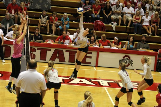 Then-junior outside hitter Erin Sekinger (12) jumps up for a spike during an exhibition match against Polish Team on Sept. 4, 2013 at St. John Arena. OSU won, 3-2.  Credit: Lantern file photo