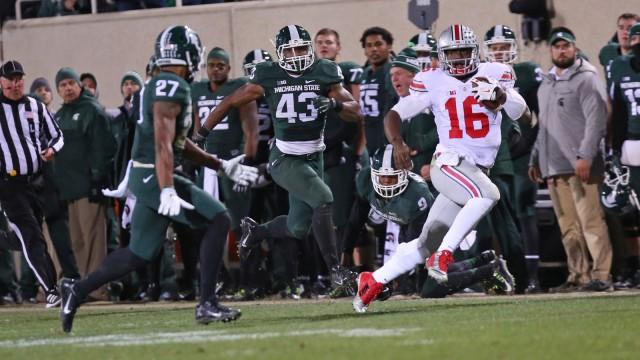 Redshirt-freshman quarterback J.T. Barrett (16) carries the ball during a game against Michigan State on Nov. 8 in East Lansing, Mich. OSU won, 49-37. Credit: Mark Batke / Photo editor