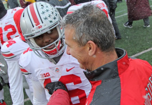 Redshirt-freshman quarterback J.T. Barrett (16) greets coach Urban Meyer after a game against Minnesota on Nov. 15 in Minneapolis. OSU won, 31-24.  Credit: Mark Batke / Photo editor