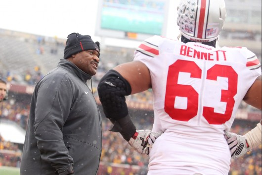 Defensive line coach Larry Johnson speaks to senior defensive lineman Michael Bennett (63) during a game against Minnesota on Nov. 15 in Minneapolis. OSU won, 31-24.  Credit: Mark Batke / Photo editor
