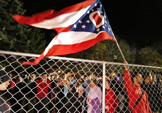A man holds an Ohio flag over fences surrounding the Mirror Lake area on Nov. 24. Credit: Yann Schreiber / Lantern reporter