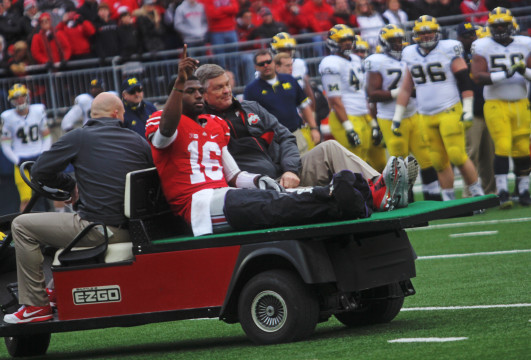 Redshirt-freshman quarterback J.T. Barrett (16) is carted away after suffering a right ankle fracture during the 4th quarter of a game against Michigan on Nov. 29 at Ohio Stadium. OSU won, 42-28. Credit: Chelsea Spears / Multimedia editor