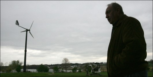 Frank Towns stands near the wind turbine he installed at his home April 9, 2010, in Louisville, Ohio. Credit: Courtesy of TNS