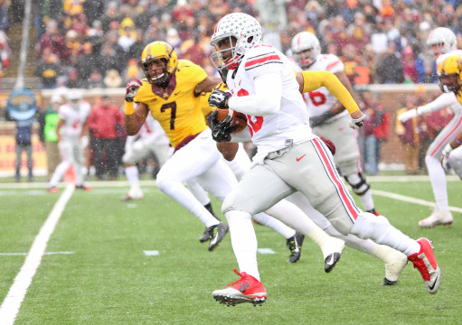Redshirt-freshman quarterback J.T. Barrett (16) carries the ball past defenders during a game against Minnesota on Nov. 15 in Minneapolis. Barrett ran for 189 yards and a touchdown and set 3 school records in OSU's 31-24 win. Credit: Mark Batke / Photo editor
