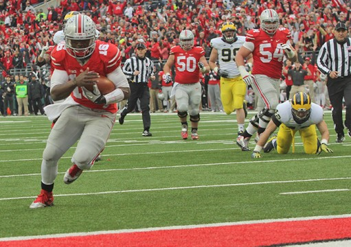 Redshirt-freshman quarterback J.T. Barrett (16) carries the ball toward the end zone during a game against Michigan on Nov. 29 at Ohio Stadium. OSU won, 42-28. Credit: Mark Batke / Photo credit