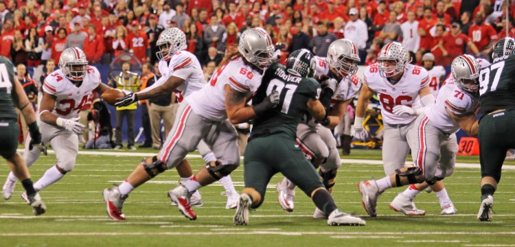Members of the OSU offense attempt to move the ball downfield during the 2013 Big Ten championship game against Michigan State Dec. 7. at Lucas Oil Stadium. OSU lost, 34-24. Credit: Lantern file photo
