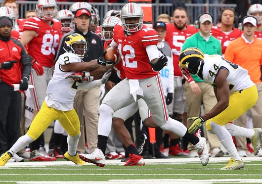 OSU redshirt-sophomore quarterback Cardale Jones (12) carries the ball as Michigan junior defensive back Blake Countess (2) and sophomore safety Delano Hill (44) defend during a Nov. 29 game at Ohio Stadium. OSU won, 42-28. Credit: Lantern file photo